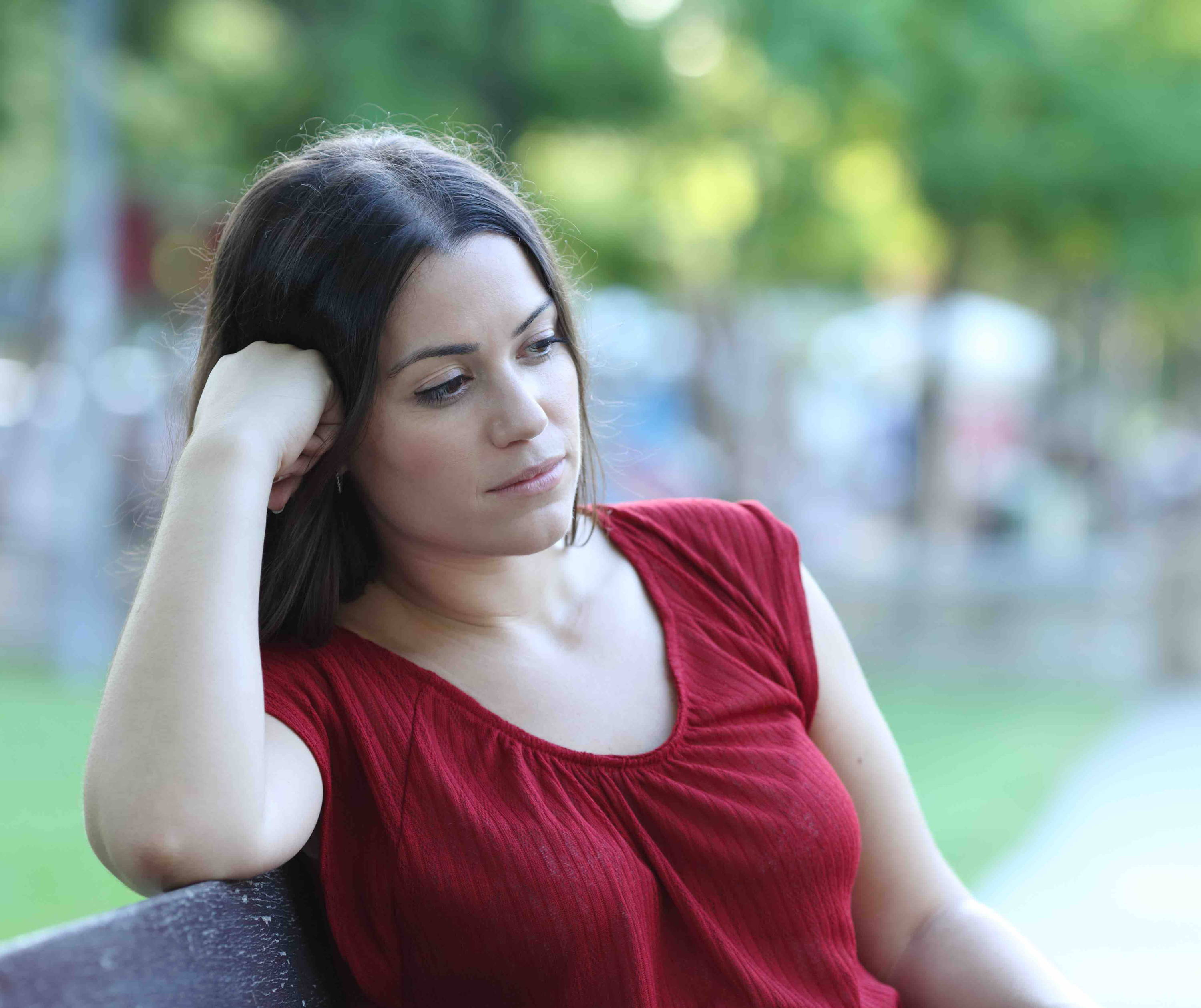 Woman on bench looking pensive