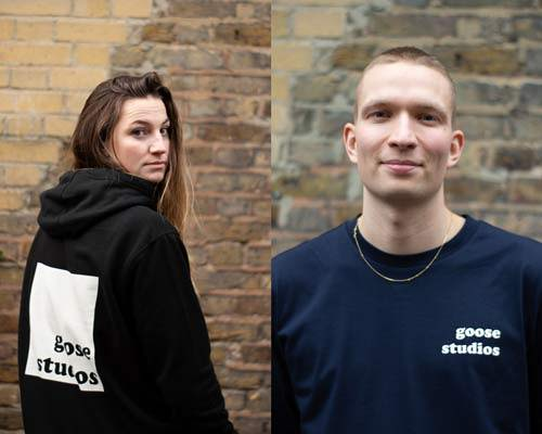 Woman wearing organic cotton black oversized hoodie with white large printed logo with Goose Studios text and man wearing navy blue organic cotton long sleeve t-shirt with Goose Studios logo, both from sustainable fashion brand Goose Studios