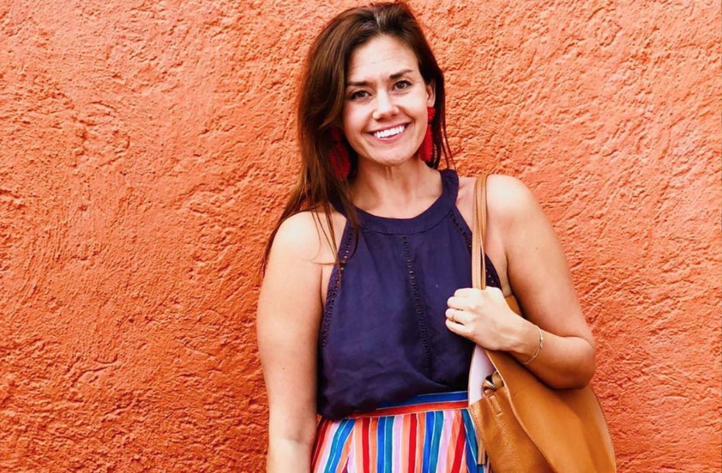 Megan Shekleton, founder of MoxxieMade, against a wall smiling and holding a purse