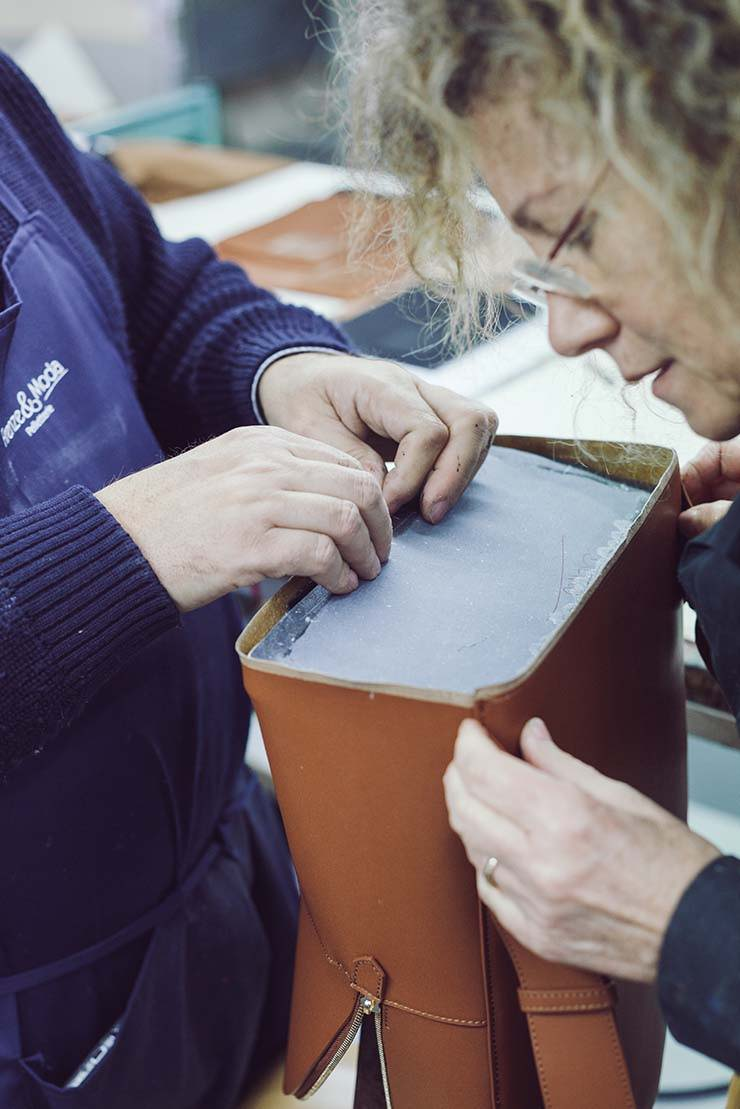 2 women creating an opus mind brown handbag in their factory in Florence