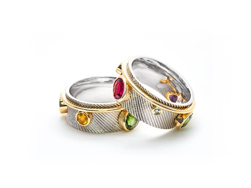 Two diagonally textured two-tone white gold or rose gold rings with ruby, peridot and citrine set in relief