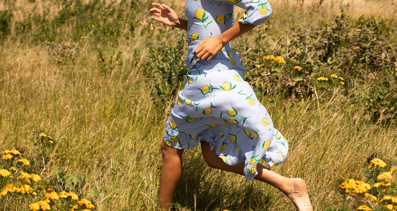 Miquita Oliver running through a field of flowers wearing YOLKE's  Lemon Calamity Dress