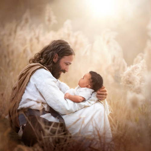 Jesus sitting in a field and holding an infant.