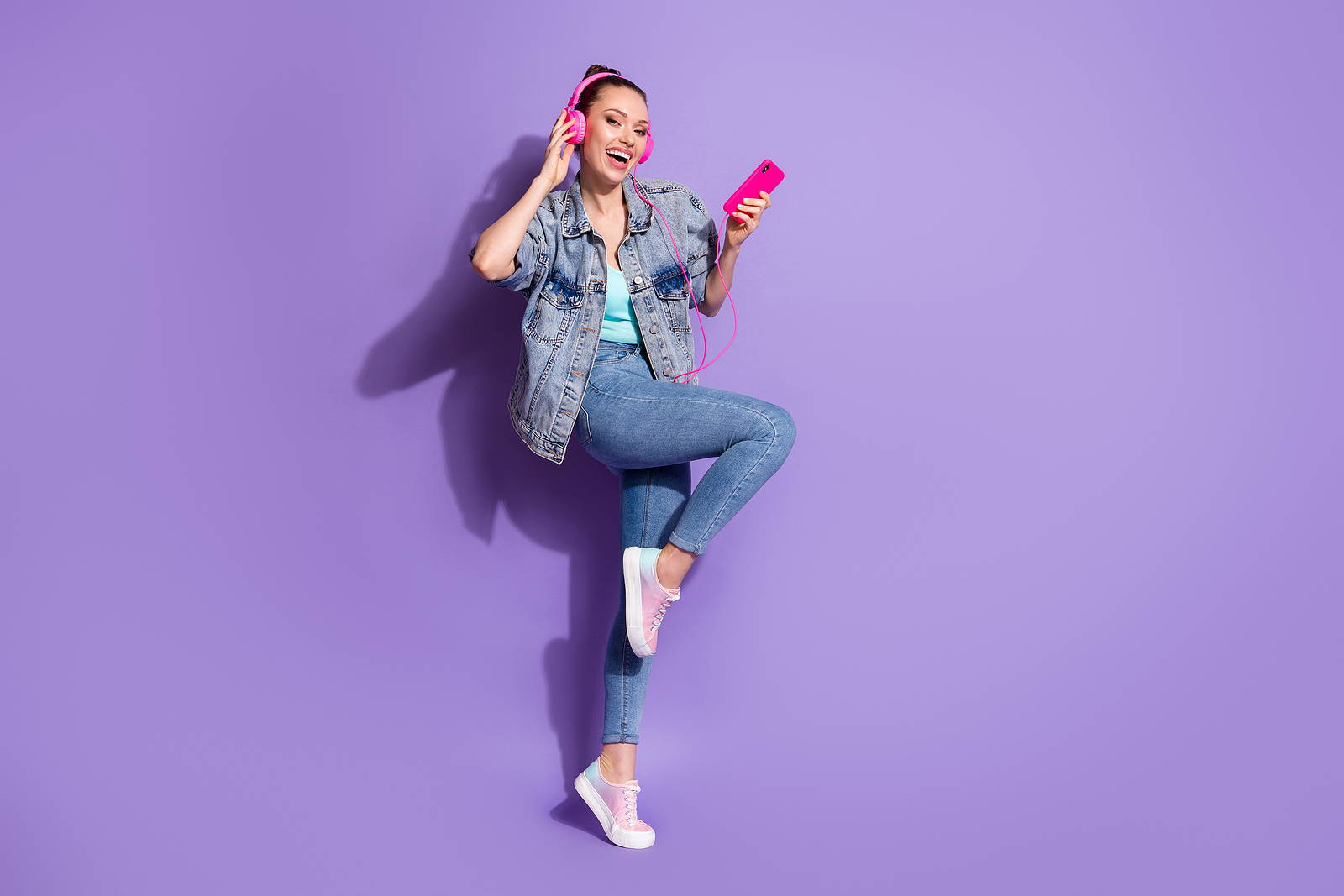 An attractive woman wearing pink headphones against a purple background, jumping in the air and smiling.