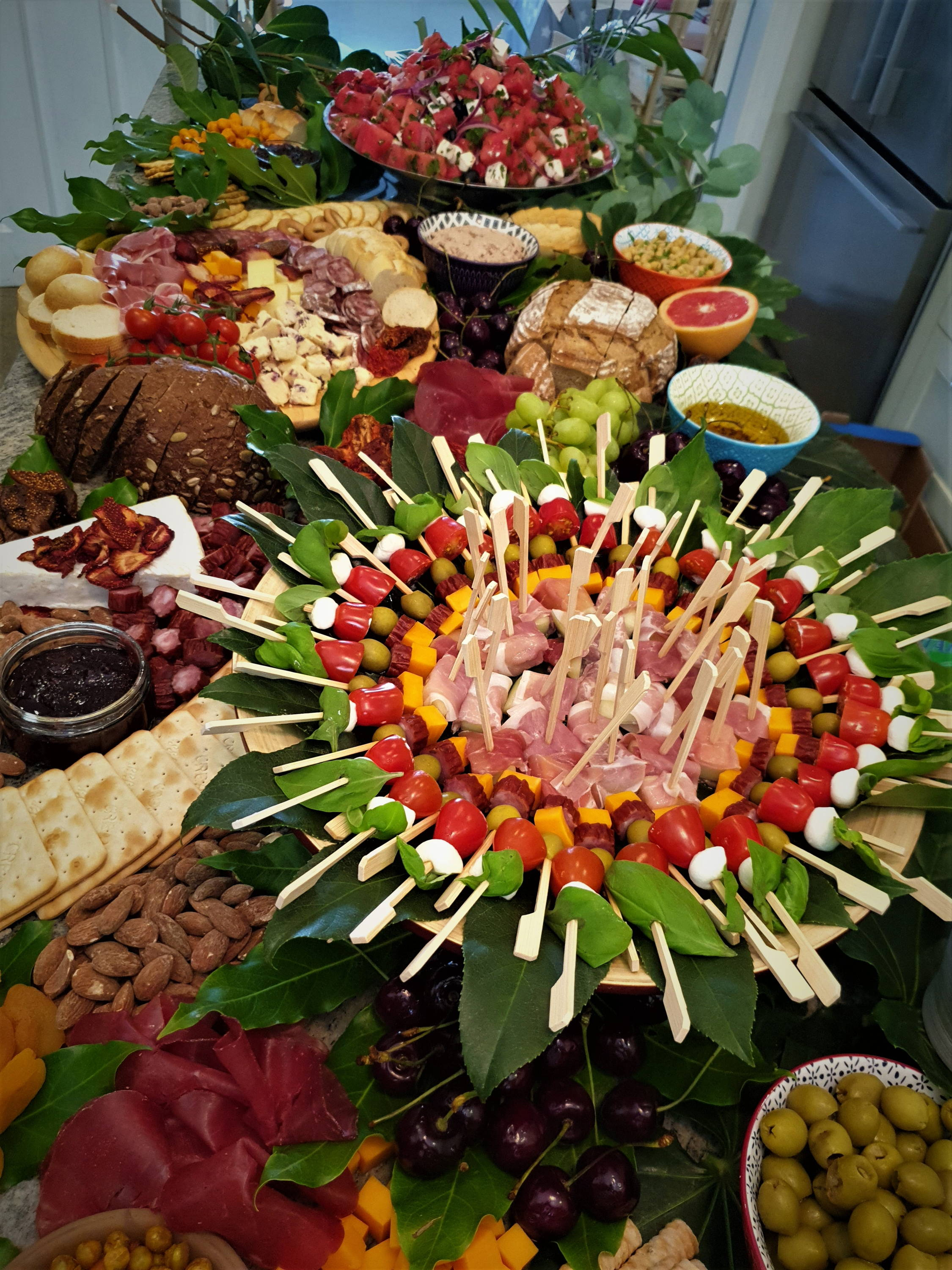 Grazing table with layers of cured meats, cheeses, fruit and vegetable. Offered by Kidbay Parties, London Loves Catering.