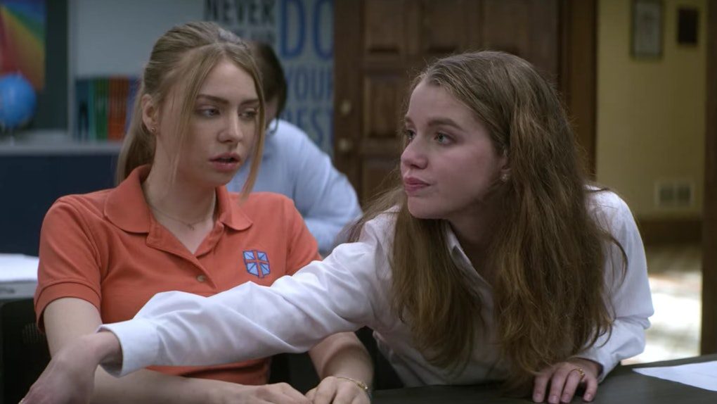 Sterling and April in a classroom. Sterling looks surprised as April deliberately reaches across her, allowing their arms to touch.