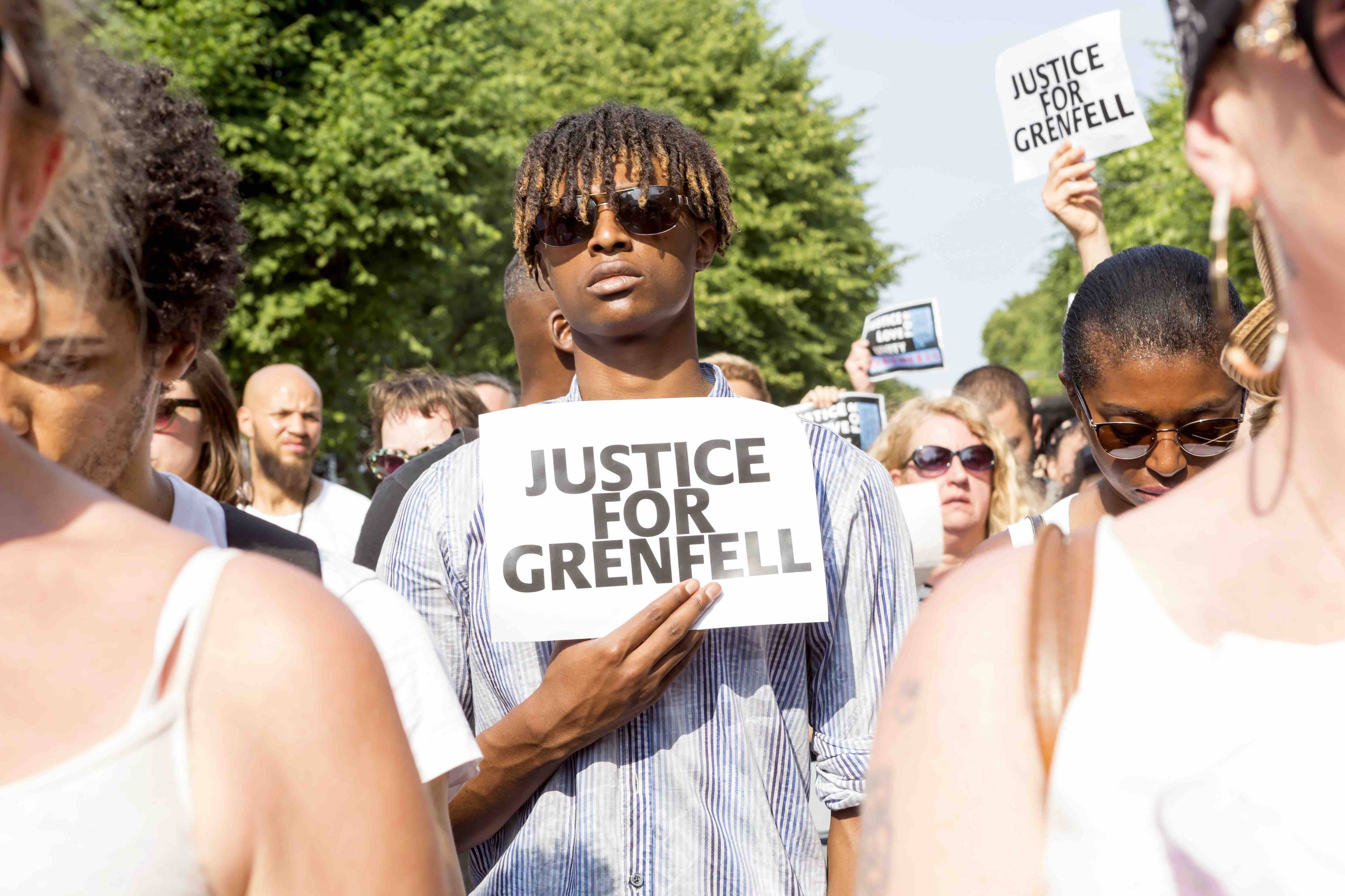 Young man in a crowd holding sign: Justice For Grenfell