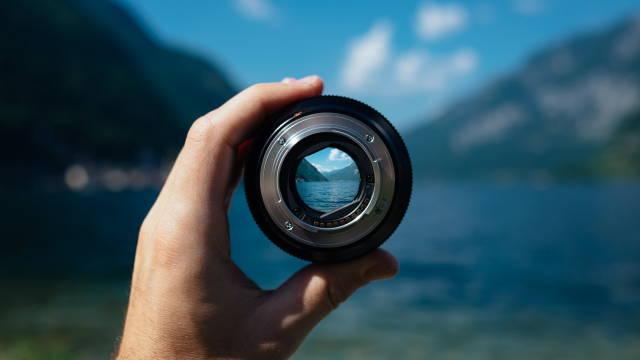 En kameralinse, som har fokus på et smukt landskab i baggrunden