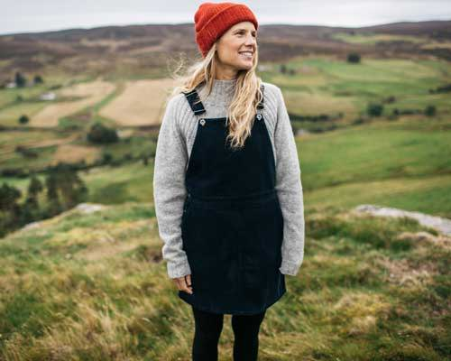 Woman wearing Finisterre Black cord dungaree dress on top of grey knit and an orange beanie hat in a countryside landscape