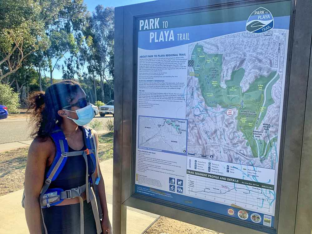 Woman looking at the Park to Playa map at Kenneth Hahn State Recreation Area