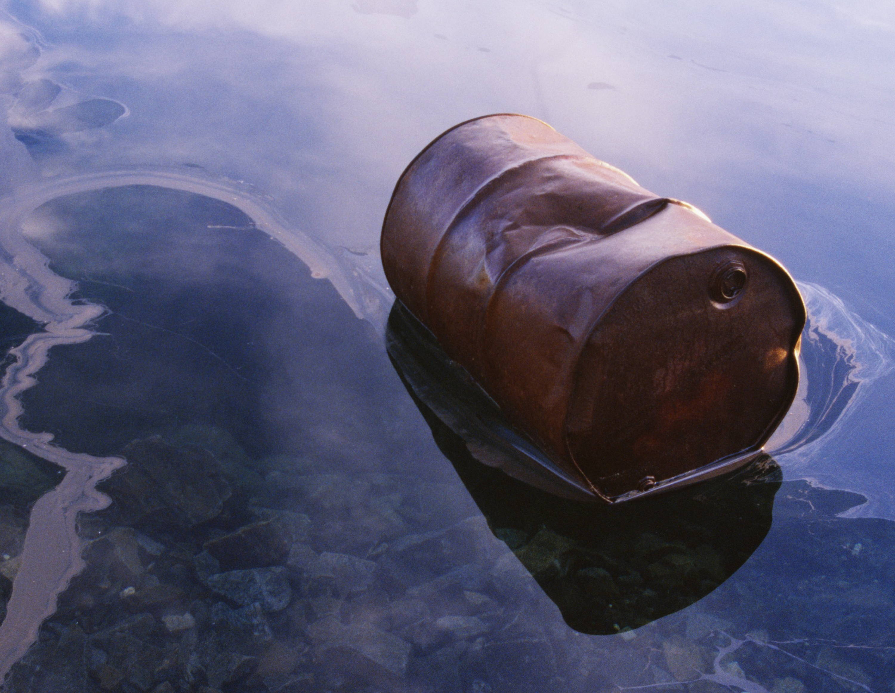 A barrel floating in polluted water