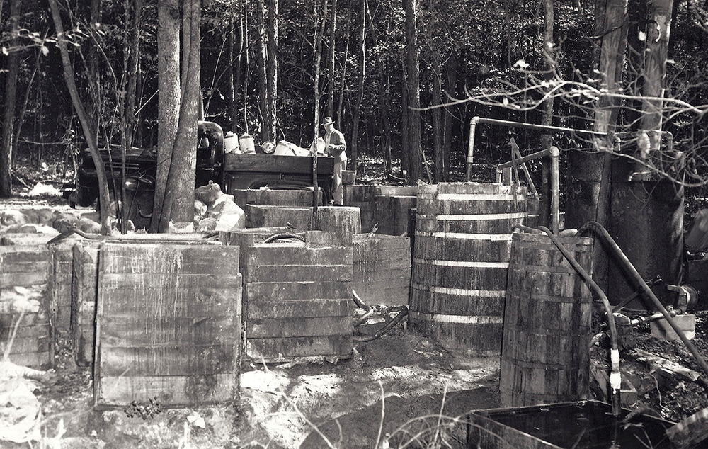 Large steam still operation located in Call's Section, Wilkes County, North Carolina. Note the 4×4 open wood fermentation boxes on left and the still, burners, thumper, and condenser on right. The Revenuer in the background looking on to his find.