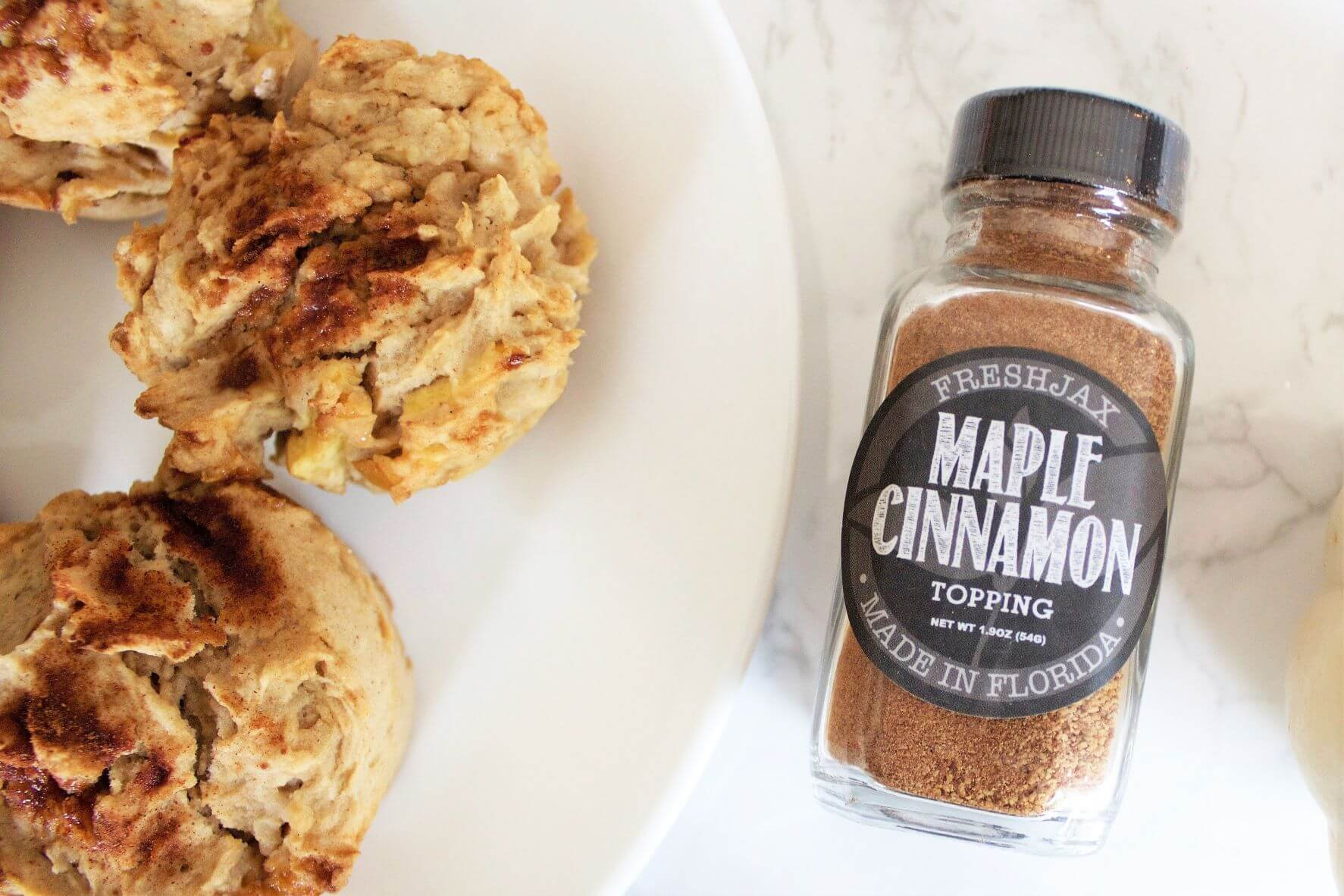 A plate of maple cinnamon apple muffins next to a sample size bottle of FreshJax Organic Maple Cinnamon Topping.
