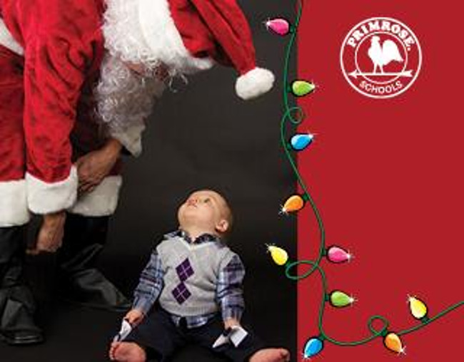 Little toddler boy sitting on the floor looks up at Santa Claus who bends over to look at him