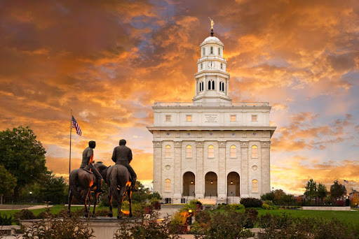 Nauvoo Temple picture featuring the statues of Joseph and Hyrum on horseback. Orange clouds in the background.