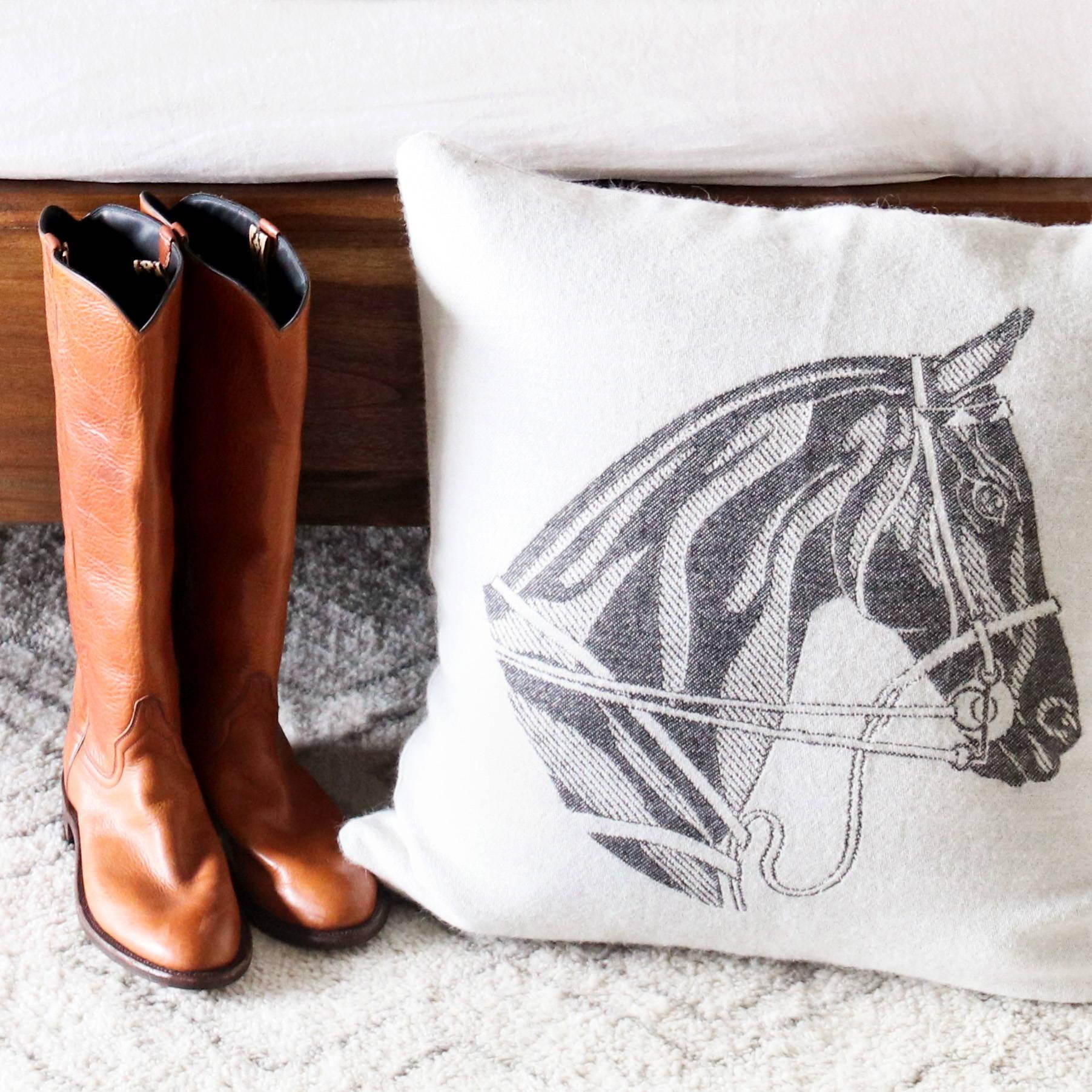 Alpaca Horse Head Decorative Pillow next to equestrian boots - Stick & Ball