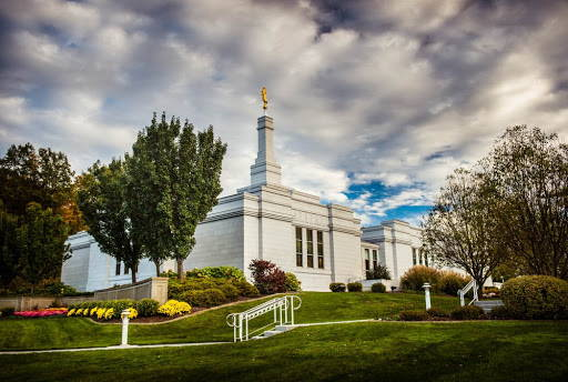 Angled photo of the Palmyra Temple. A patch of blue sky interrupts the cloudy sky.