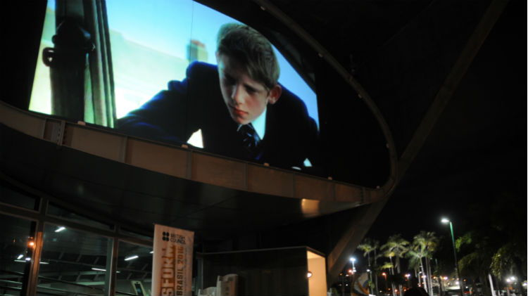 Billy Elliot film projected on to a building at night.