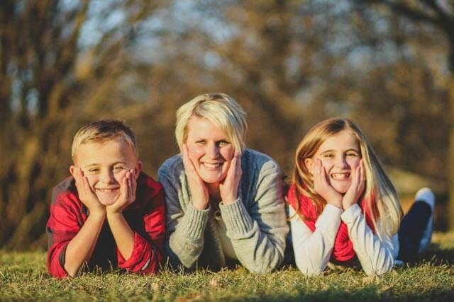 A photo of Rachel and her two kids (a son and daughter). They are all three posing with their faces in their hands against a background of fall colors. Big smiles all around.