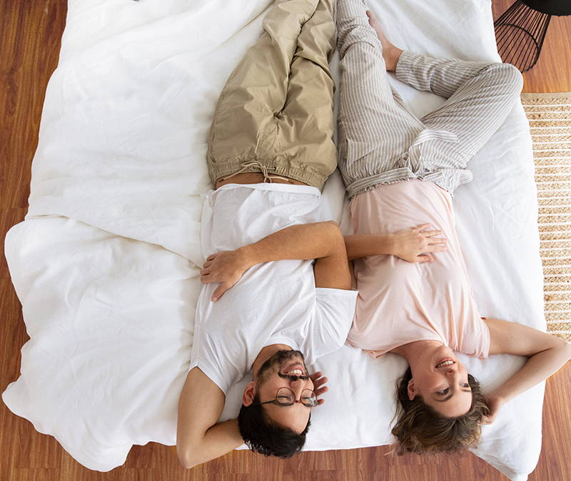 Man and woman lying on Real Bed. Image