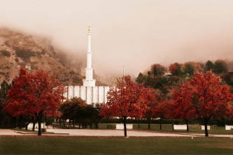 Provo Temple surrounded by red trees and  against a foggy mountain.