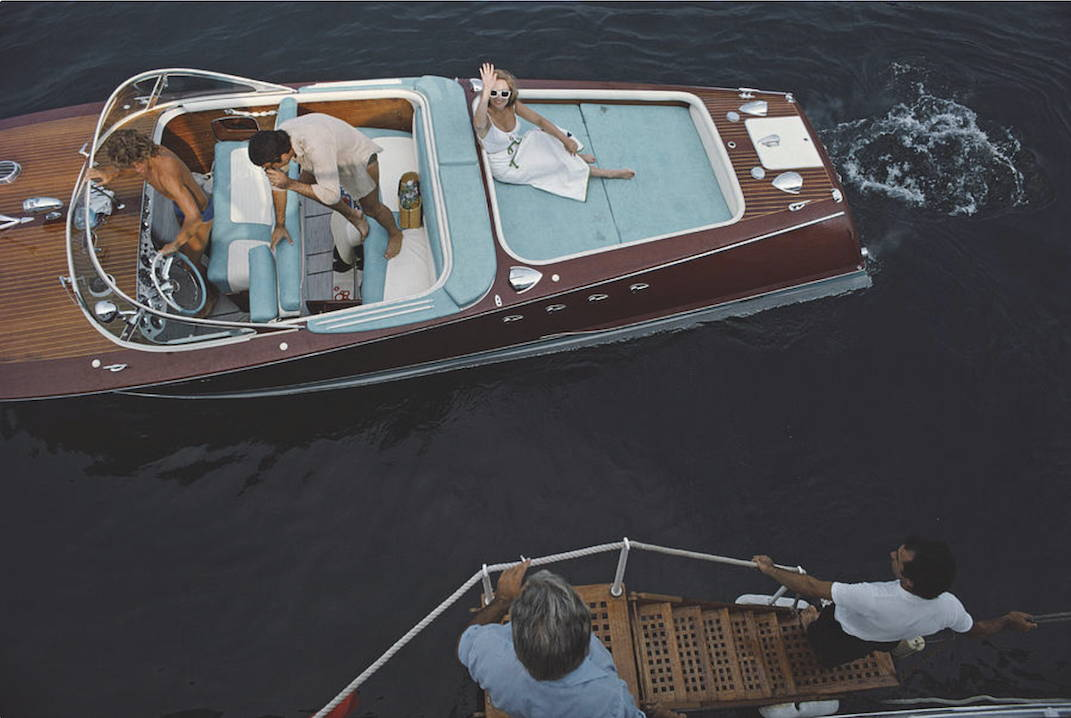 A lady waves at the camera from below in a boat as friends go for a cruise around the waters of Monte Carlo