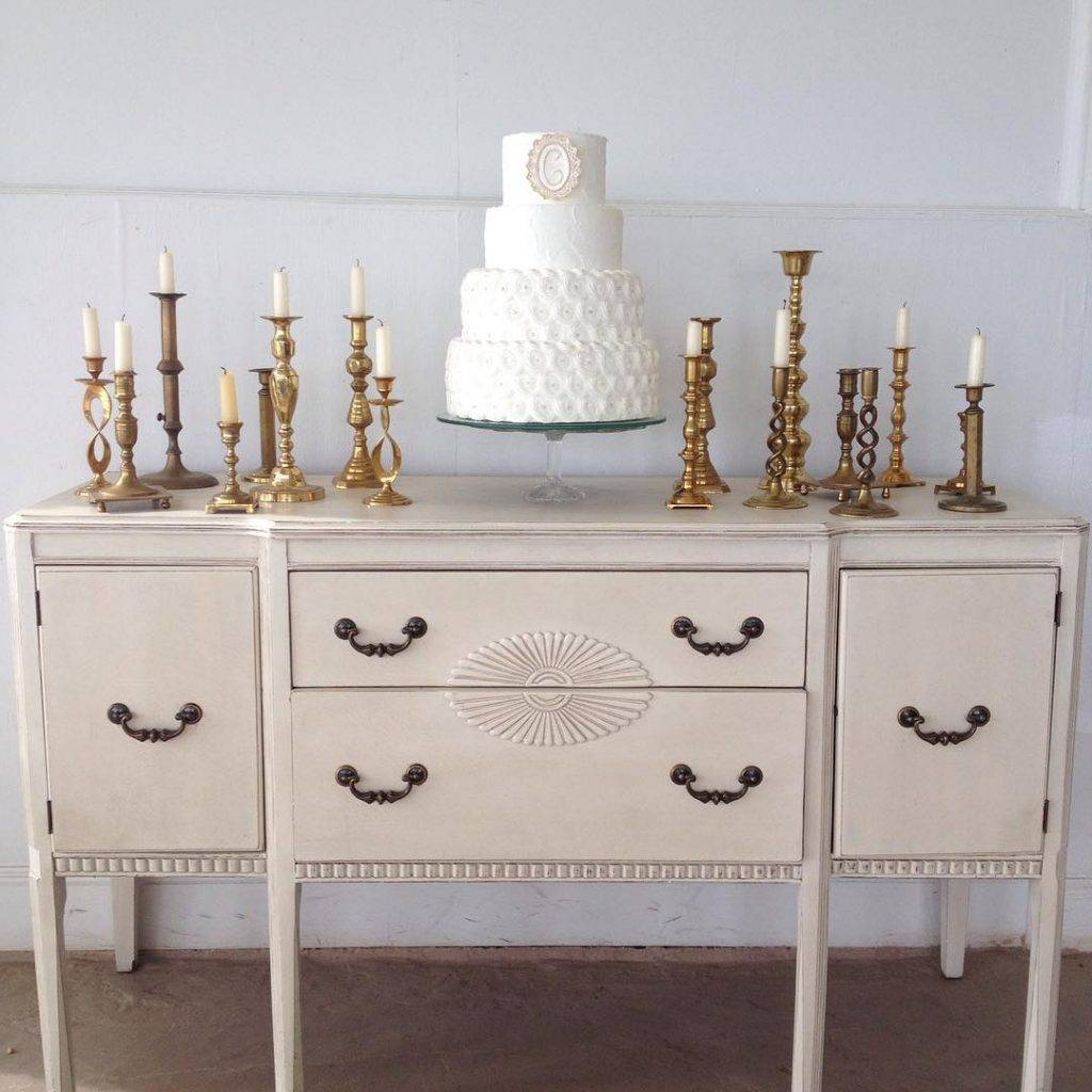 Three tiered wedding cake on a table surrounded with brass candle stick holders.