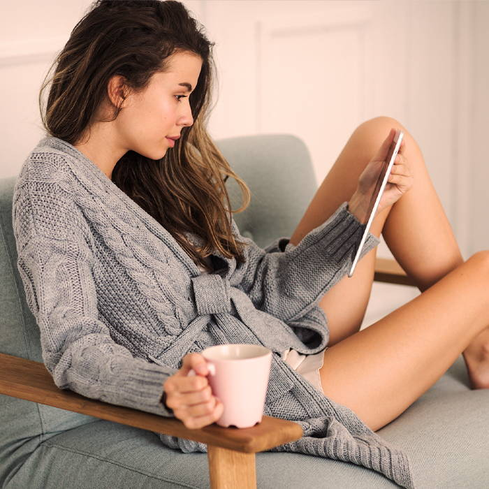 women with smooth legs in grey robe reading