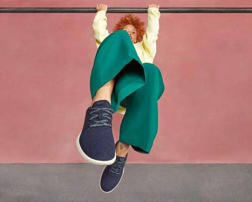 Woman swinging on a bar wearing navy blue Allbirds woollen sneakers