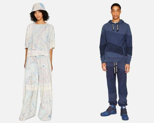 Woman wearing wide leg trousers, matching half sleeve top and bucket hat all made from recycled silk map fabric and man wearing organic cotton blue asymmetric stripe hoodie and sweatpants with Raeburn branding