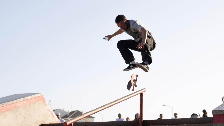 Photo d'un skater qui fais un tricks avec sa board (ollie ou kickflip) avant de slider sur la barre du skatepark. Il porte un t-shirt de la marque de skate Saïmiri-SB.