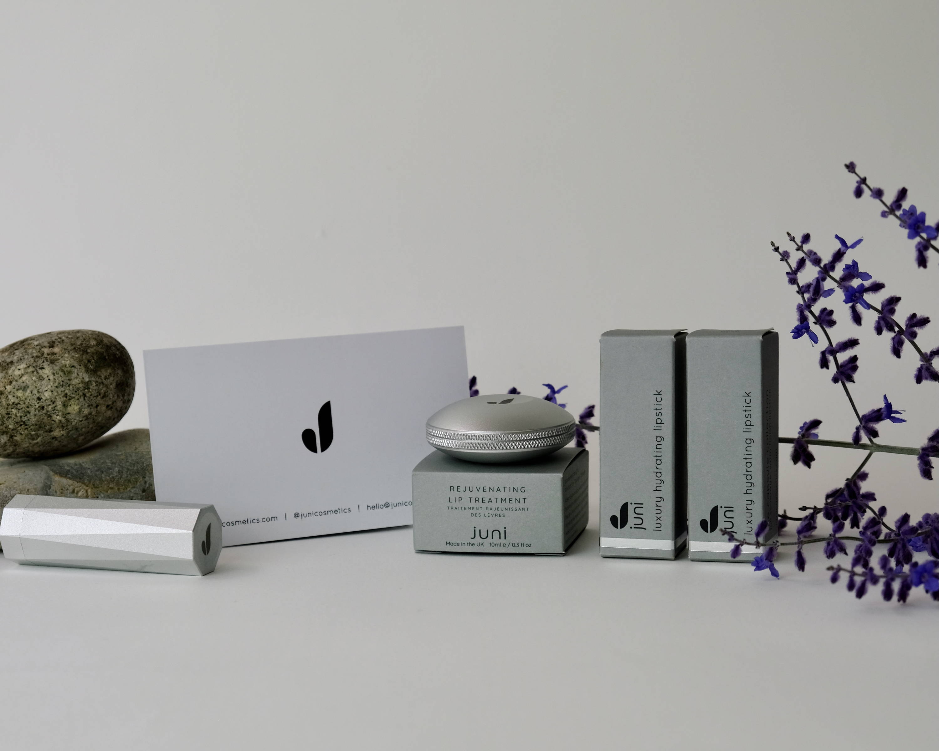 Image of a selection of Juni products displayed with some flowers and decorative rocks