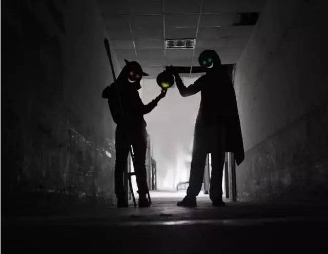 Two ghosts carrying lamps in the dark corridor