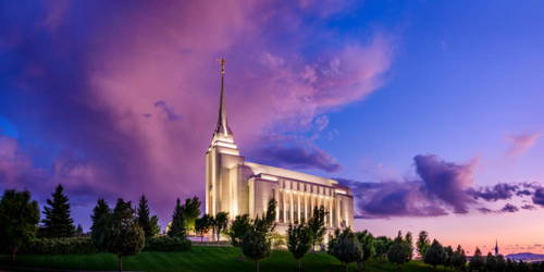 Photo of the Rexburg LDS Temple standing against a purple and blue sky.