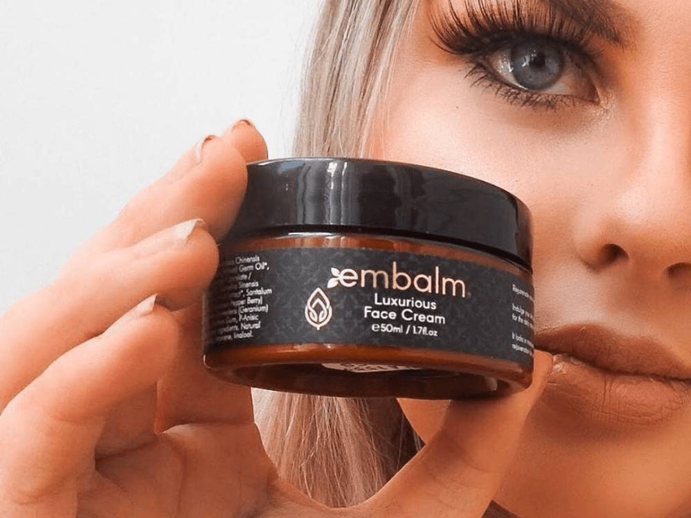 close up image of woman holding Embalm Skincare Luxurious Face Cream