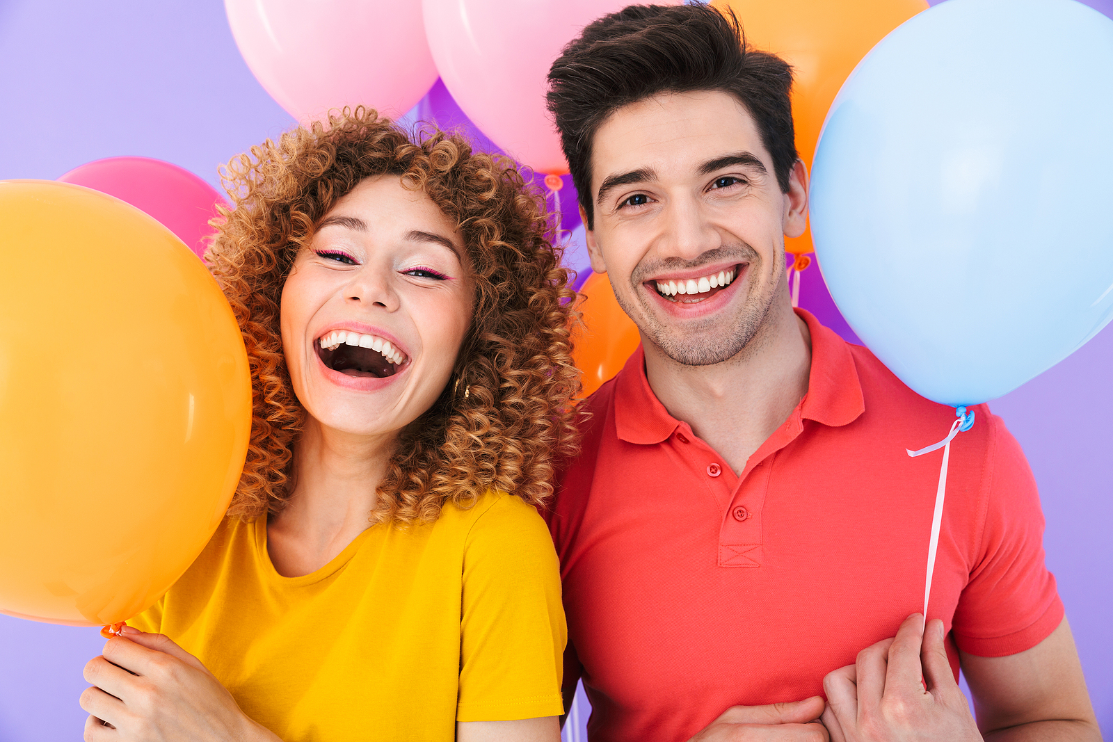 A happy man and woman smiling at camera while standing with multicolored air balloons isolated over violet background.
