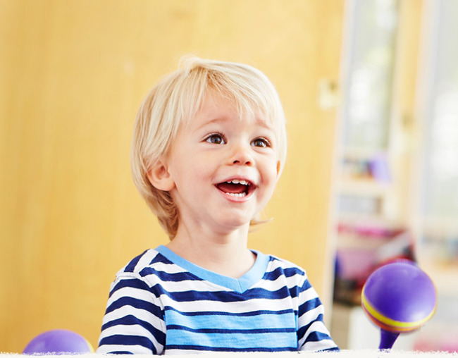 Young toddler excitedly plays the shakers