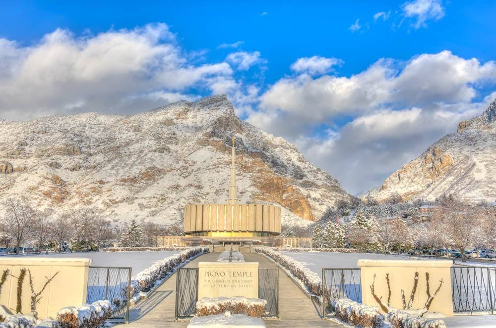 Provo Temple beneath a blue sky surrounded by snow