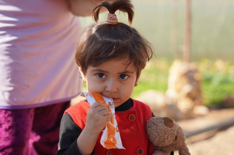 Two-year-old Syrian girl eating a nutritional peanut paste from WFP