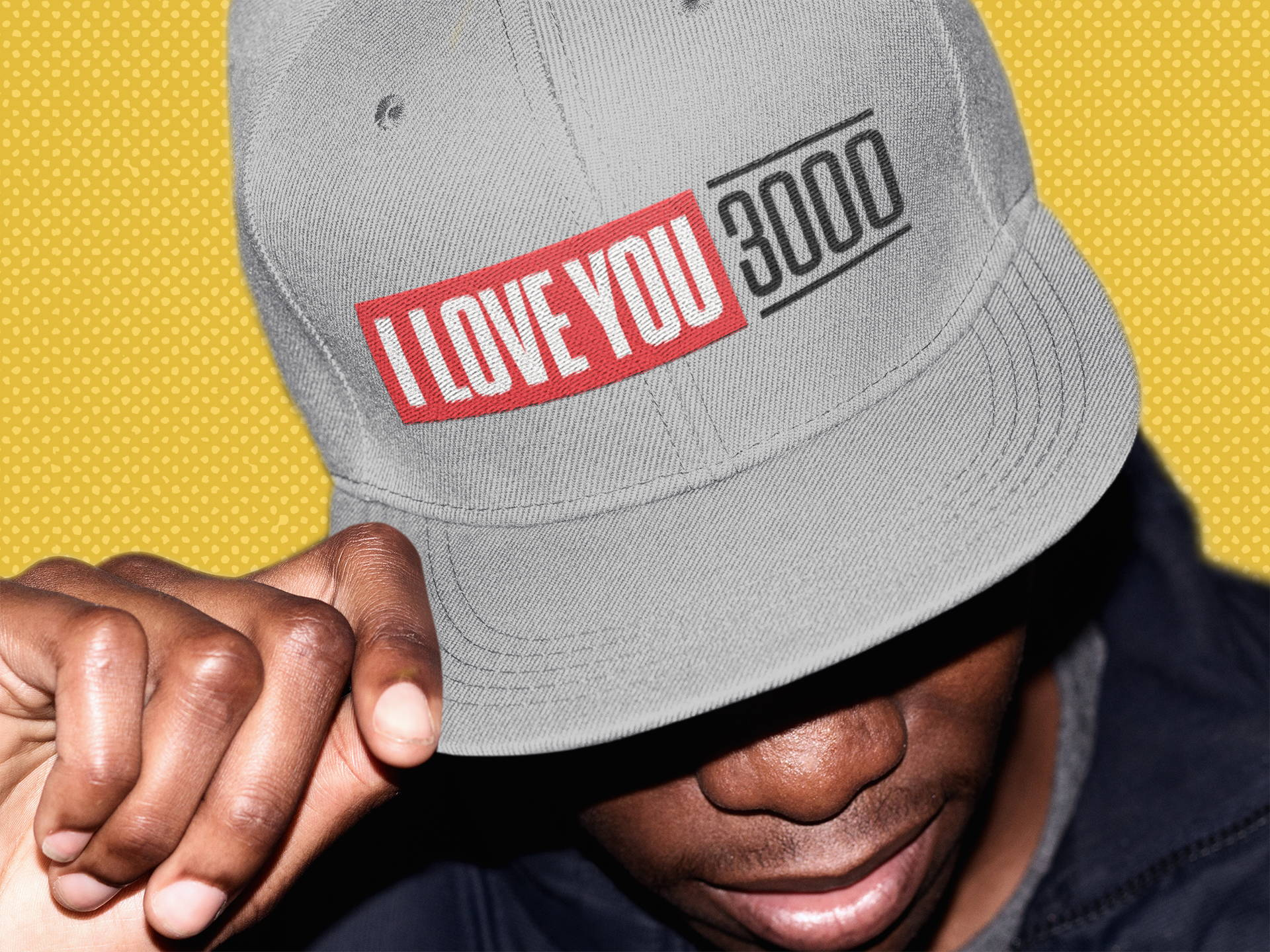 "Man wearing silver ""I Love You 3000"" snapback hat."