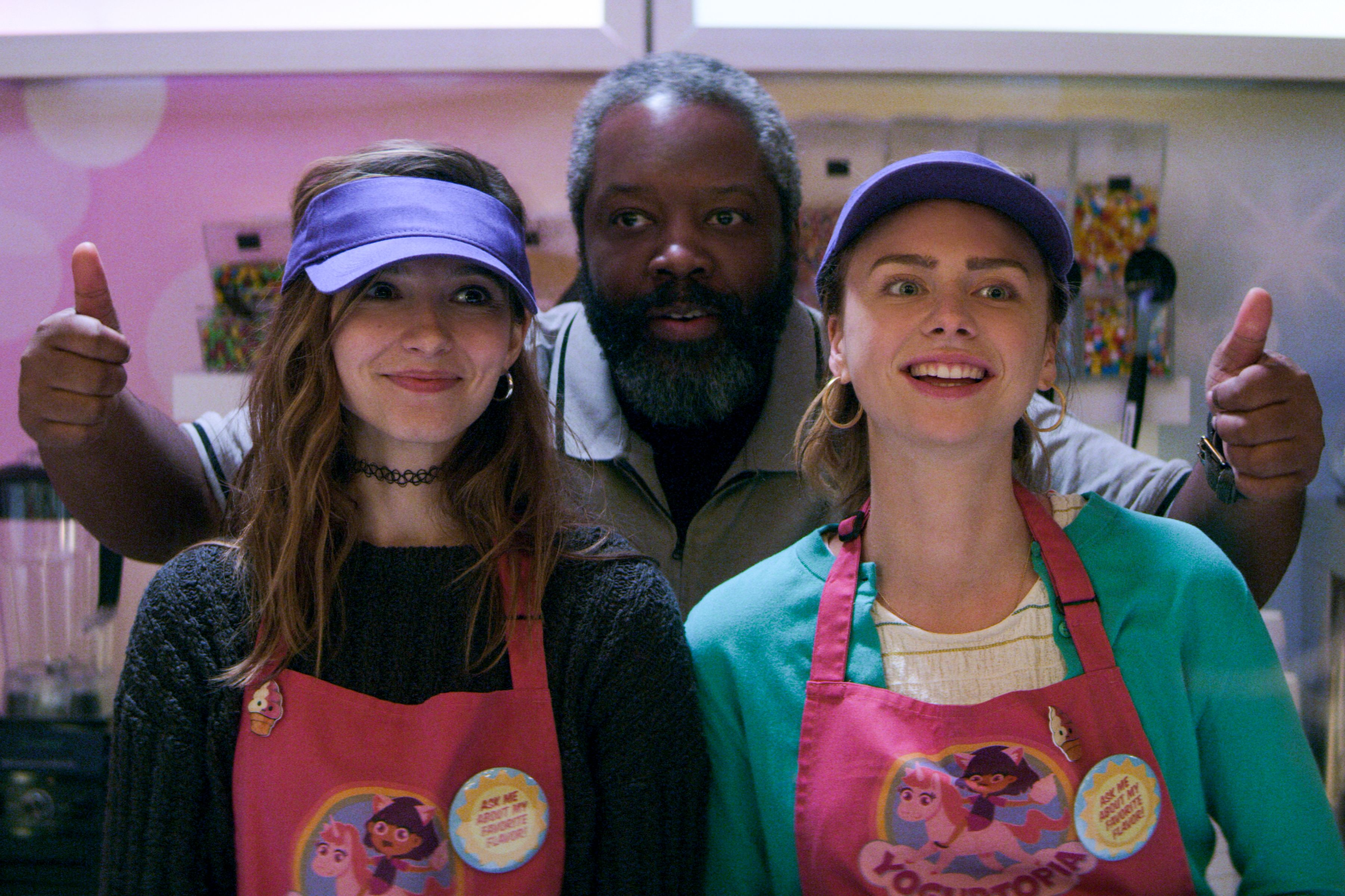Blair Wesley, Terrance Coin, and Sterling Wesley smiling and working in a frozen yogurt shop.