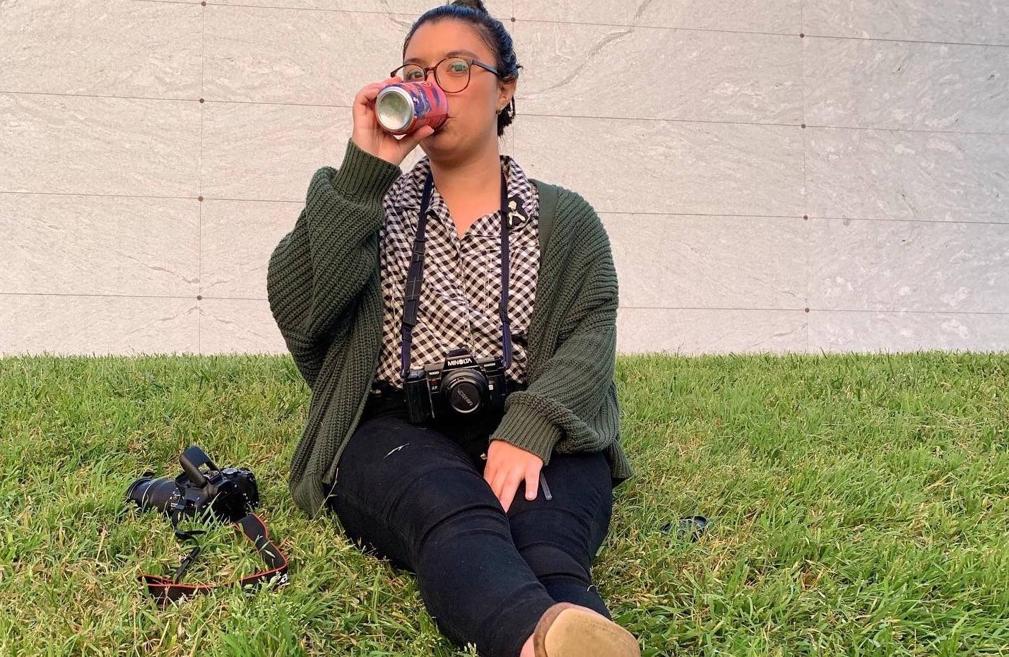 Reina is sitting on the grass next to a camera with one around her neck too. She has glasses on, her hair in a bun, and is sipping from a can.
