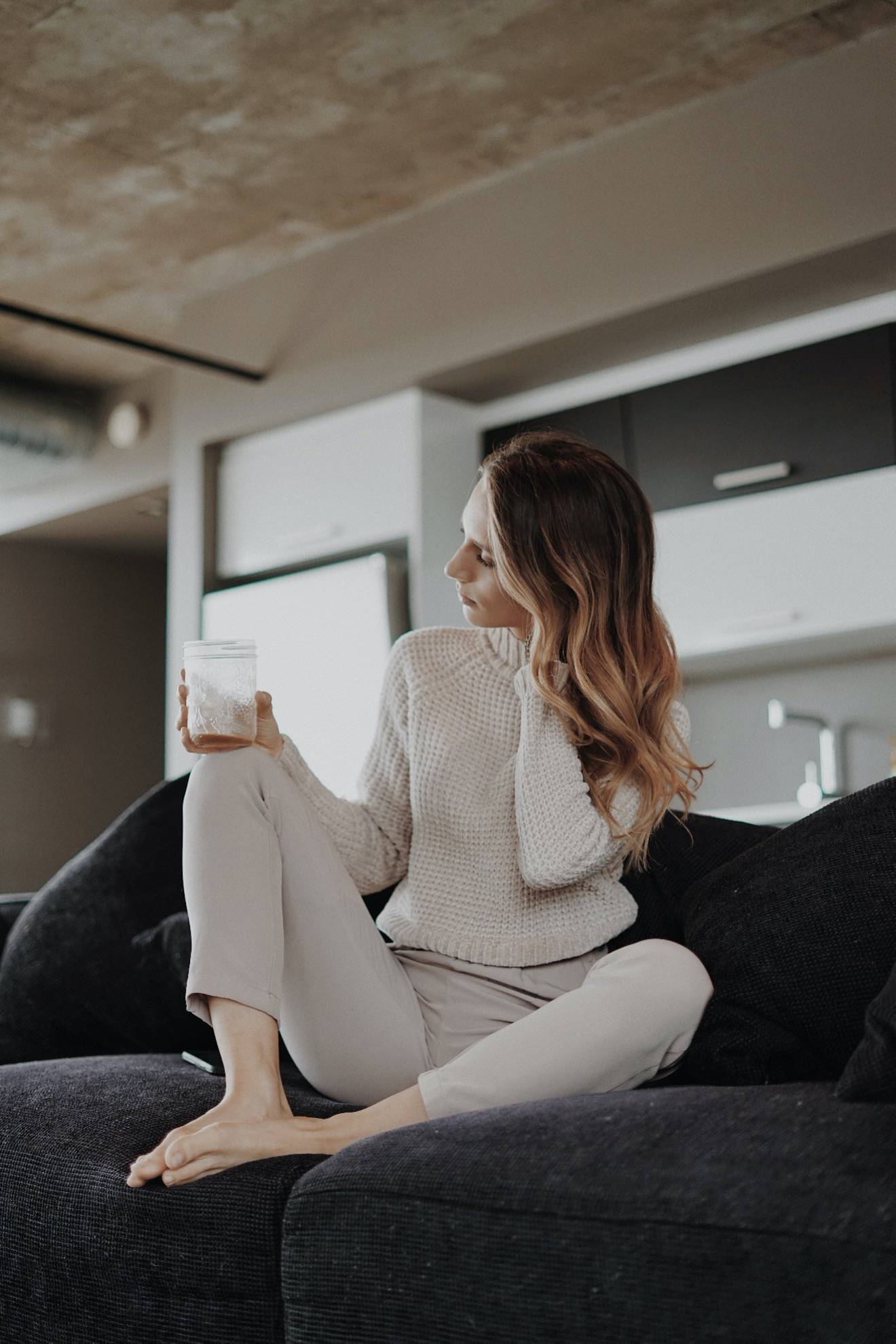 Woman sitting on a black couch drinking coffee