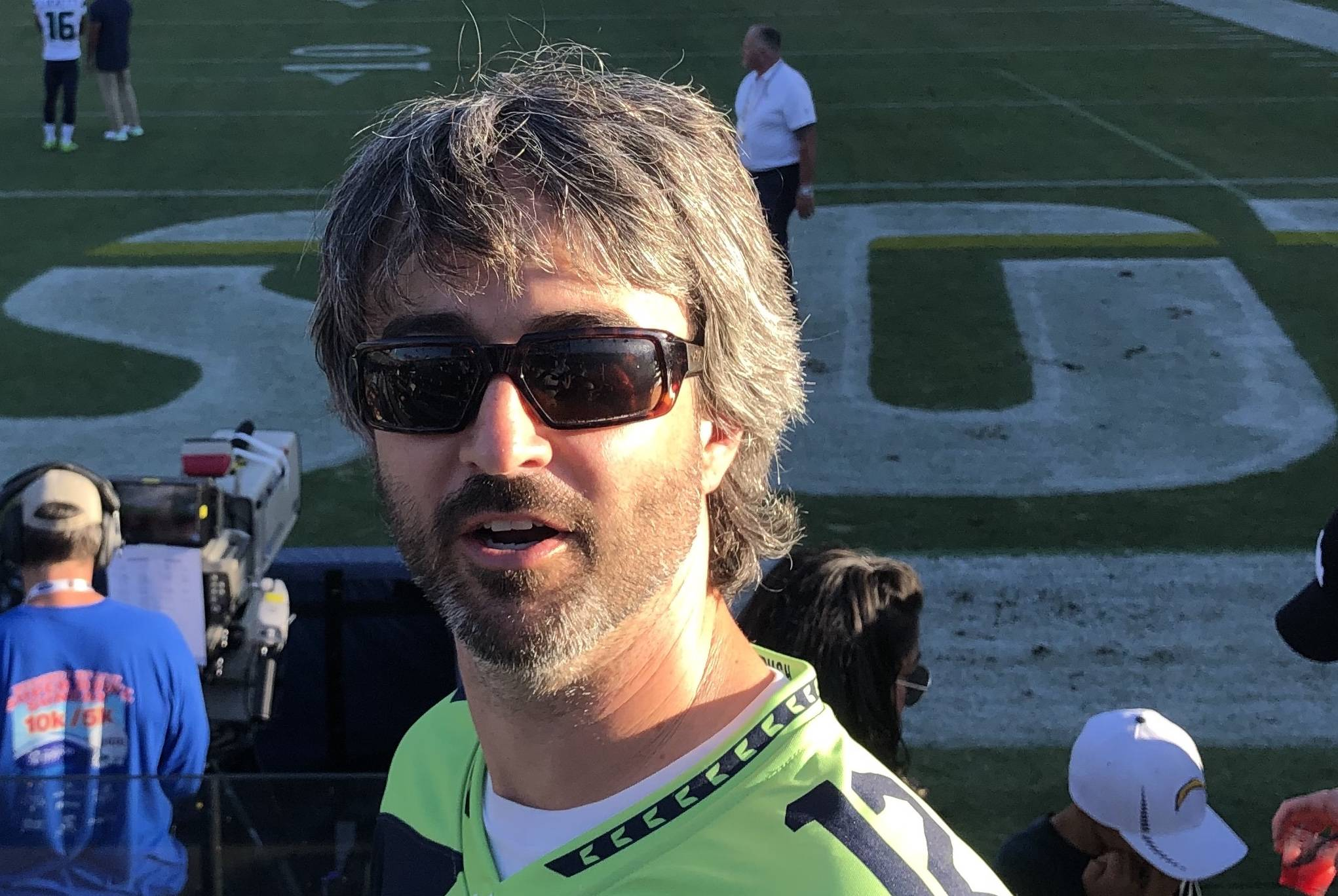 Keith is half turning toward the camera with sunglasses on at a Seahawks game. The sun is lighting half of his face.