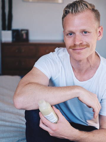 man with short hair and mustache holding a Davines hair product in a bedroom setting