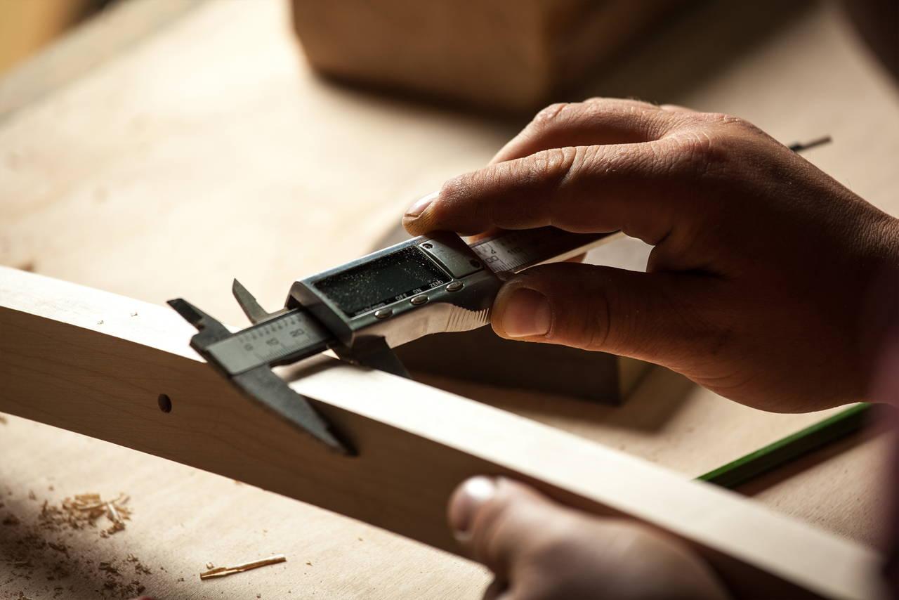 Amish craftsman measuring a piece of wood while making furniture