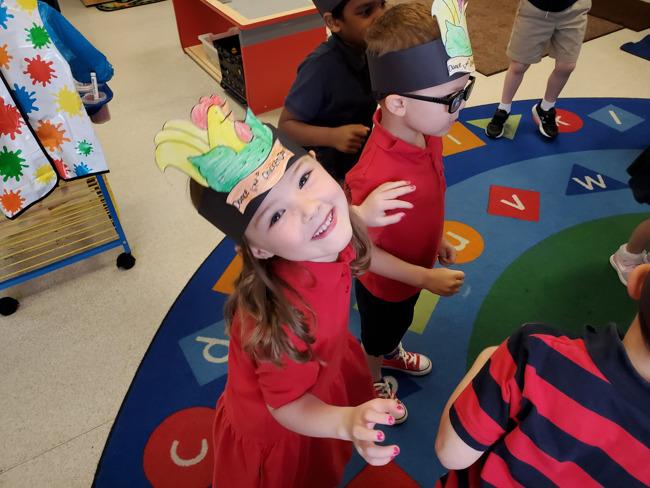 kids in hats dancing in classroom
