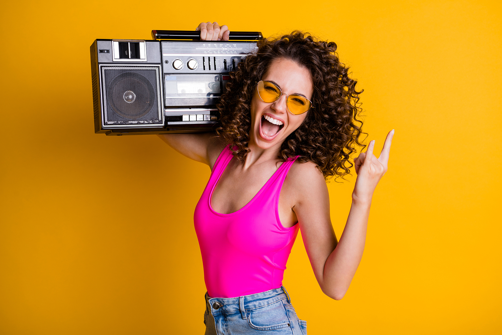 Photo of cool youngster lady with wavy hairdo listening to music holding a retro boom box.