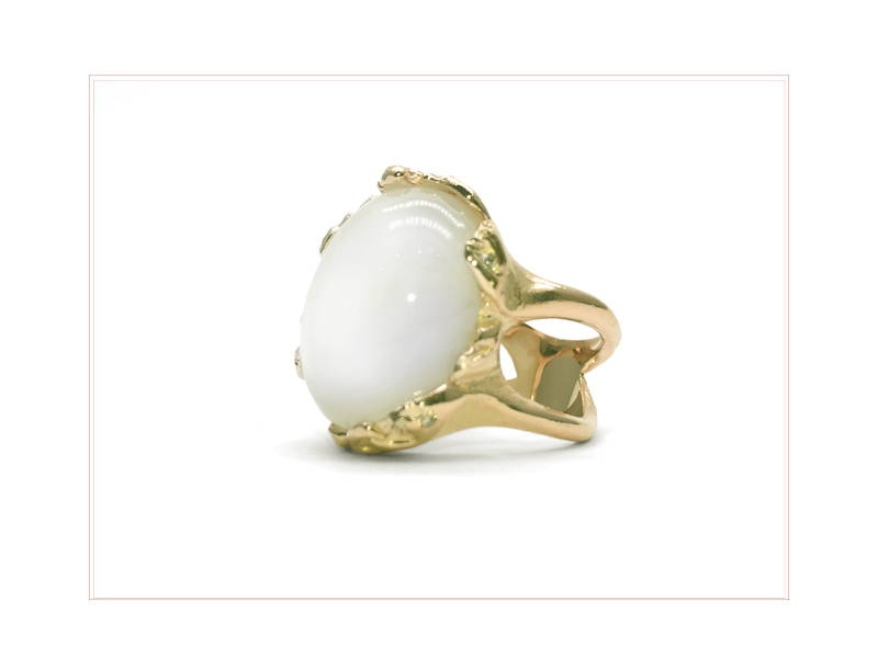 Large quartz stone mounted on a ring with irregular yellow gold rings