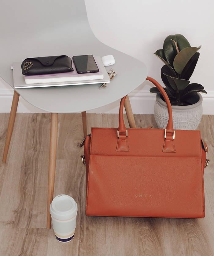 The terracotta Evora work bag near a chair, a coffee cup and a plant